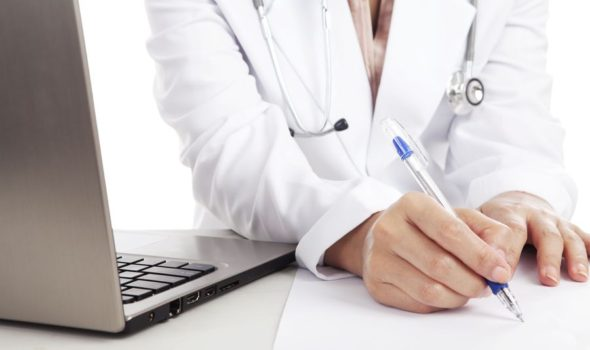 Doctor woman with stethoscope and laptop writing on the paper